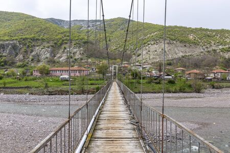 Very old and rusty suspension bridge over Borovitsa river in the Rhodope mountain in Bulgaria