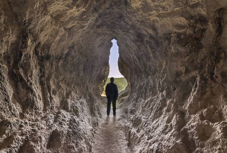 Human birth and light at the end of the tunnel concept. Man standing at the end of a small cave.