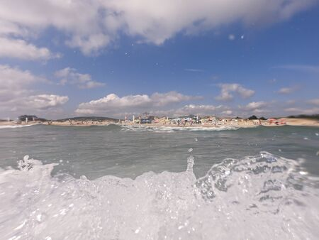 Wave crashing in front of the camera. Beautiful blue sky with clouds in the background.