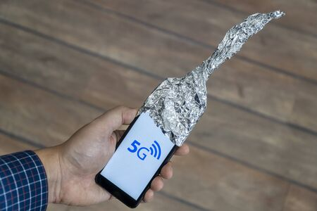 5g network danger concept. Smartphone with antenna made out of aluminum foil to block the signal. Danger sign is displayed on the phone.