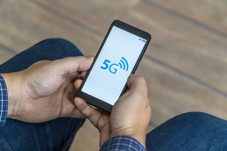5g network danger concept. Man checking his smartphone with 5g network and warning sign displayed on the phone.
