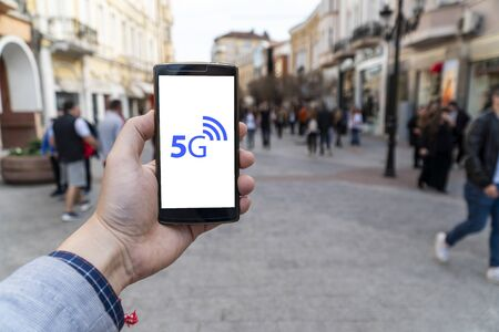 5g network danger on the street. Man holding smartphone with 5g and danger warning sign on it