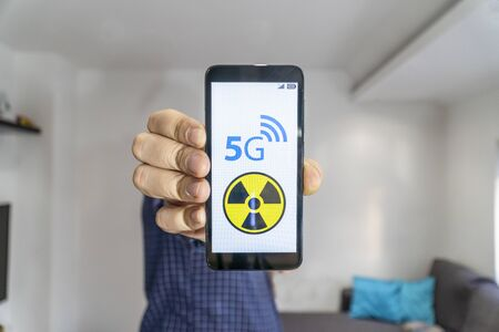 5g network danger indoors. Man shwing smartphone to the camera with 5g and danger warning sign on it