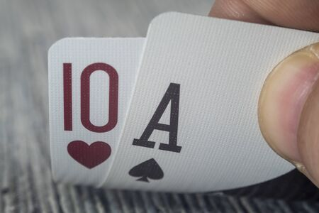 Low angle closeup view of a male hand picking up and showing cards from a casino table