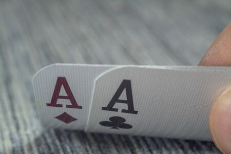 Low angle closeup view of a male hand picking up and showing cards from a casino table Stock fotó