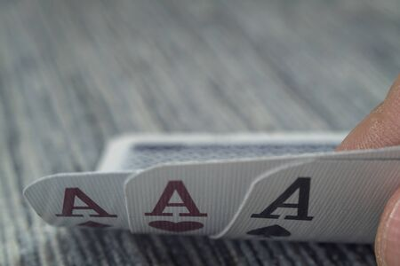 Low angle closeup view of a male hand picking up and showing cards from a casino table Stock Photo