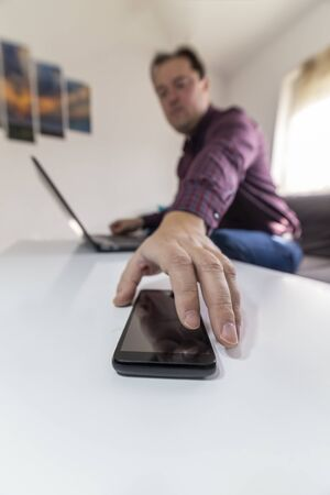 Low angle view of a man working on a laptop and reaching for his smartphone. Getting a call concept. Stock Photo