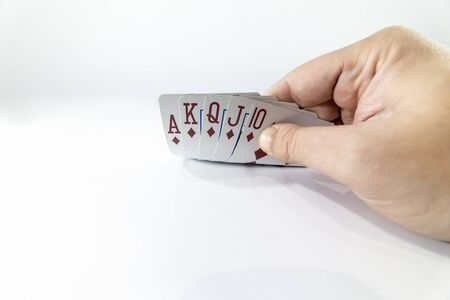 Low angle view of a hand showing poker cards isolated on white background. Gambling concept. Stock Photo