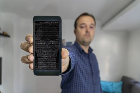 Man shwing smartphone to the camera with AI bot face on the screen
