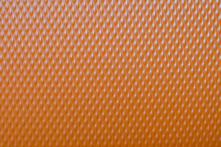 Extreme macro of an orange plastic suitcase cover pattern Stock Photo