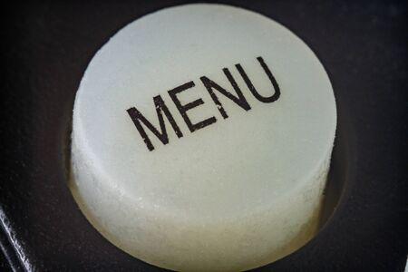 Extreme macro shot of a white menu buttin on a TV remote control