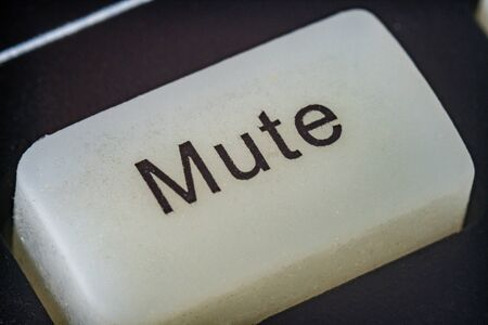 Extreme macro shot of a white mute button on a TV remote Stock Photo