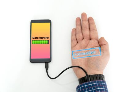 Augmented human hand connected to a smartphone via usb cable and transferring data. Hologram notification appearing on the hand