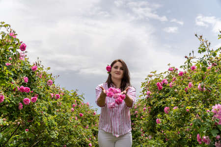 Young woman throwing Bulgarian pink roses in a garden with beautiful clouds in the background