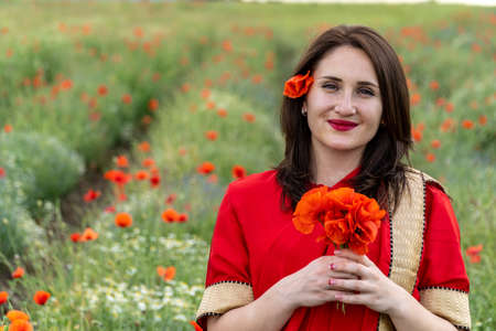 Young woman dressed in a traditional Indian costume called Sari walking in a red poppy flower field Stock Photo