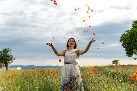 Young woman in a white dress throwing red poppy flowers at the camera