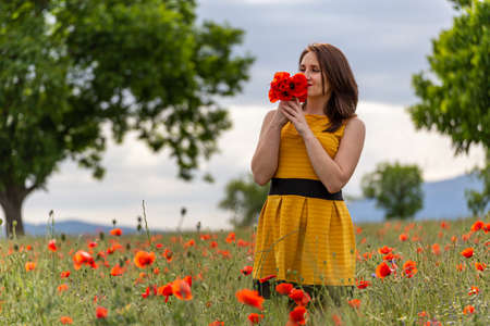 A young woman in a yellow dress in a poppy flower field with beautiful clouds in the background