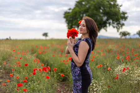A young woman in a blue dress in a poppy flower field with beautiful clouds in the background Stock fotó