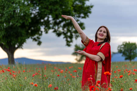 Young woman dressed in a traditional Indian costume called Sari walking in a red poppy flower field Reklamní fotografie