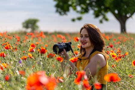 Young woman in a yellow dress holding a camera and taking pictures of a red poppy flower