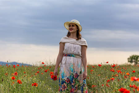 Young girl dressed in a white dress and a hat walking around a red poppy field Stock fotó