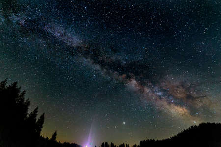 Beam of light pointing at the Milky way galaxy. UFO singal concept.