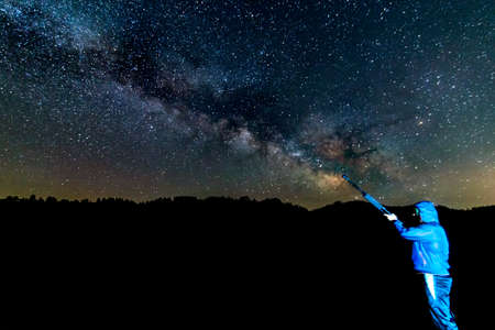 Person painting the Milky way galaxy with a brush concept