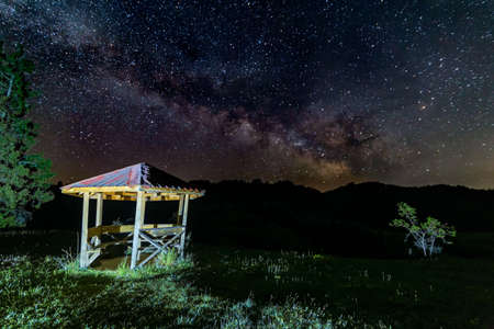 Small gazebo in the mountain with a Milky way galaxy in the background