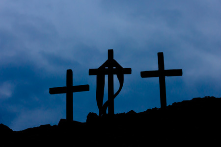 three wooden crosses on the mountain