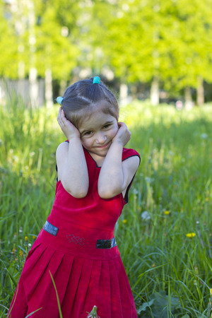 little girl in a red dress on a green meadow photo