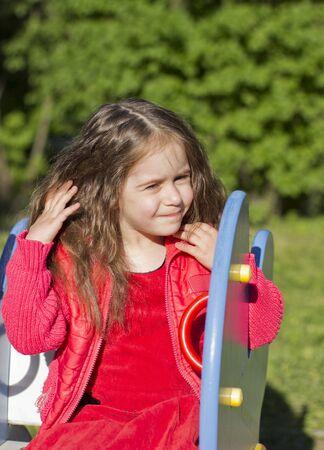 disheveled: little girl straightens her hair disheveled
