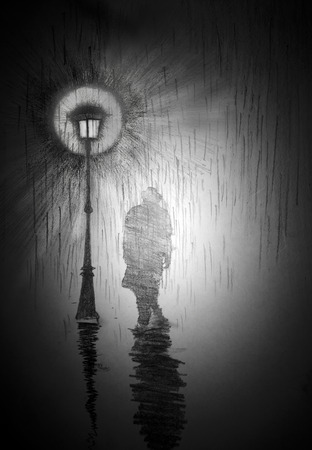 man under a street lamp with rain Stock Photo