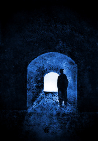 man standing alone: a man in a hat and coat in a dark passage Stock Photo