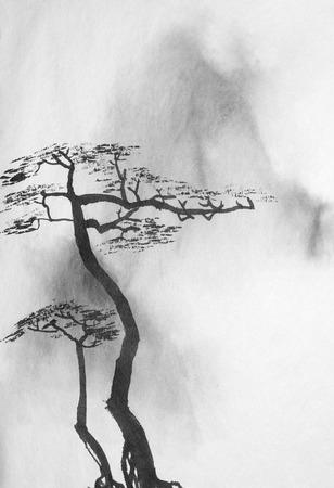 deux pins solitaires sur fond de montagnes brumeuses Banque d'images