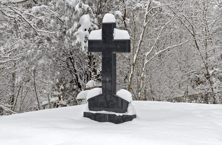 Black granite cross in the winter snow-covered forest