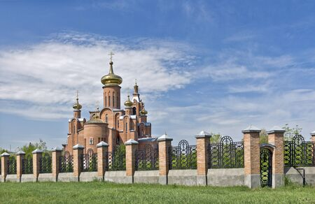 Cathedral with gilded domes against the blue sky behind the iron fence  Stock Photo