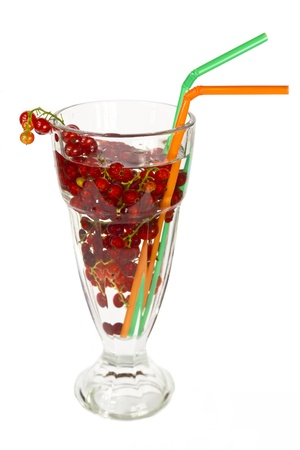 Red currants in a glass beaker with tubes for a cocktail on a white background