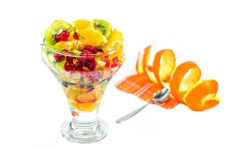 Fruit salad with kiwi, oranges, rafruit saladspberries and currants on a white background