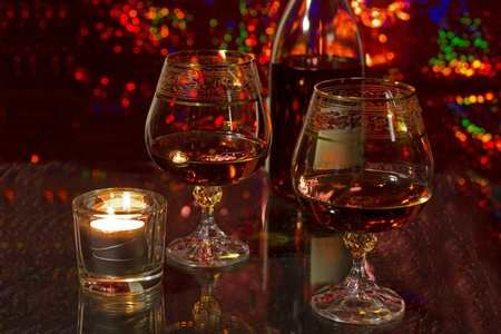 A bottle of brandy, two crystal glasses and a burning candle