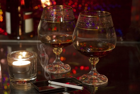 Two glasses of brandy and a cigarette and candle on the table