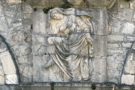 Old bas-relief of a woman on the stone wall