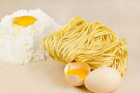 Noodle, flour and eggs on the table