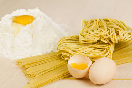 Noodles, spagetti, flour and eggs on the table   Stock Photo