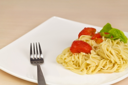 Noodle with tomatoes and lettuce on a white plate