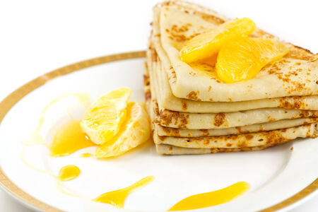 Folded pancakes with orange syrup triangle on white plate. Stock Photo