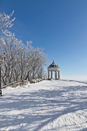 Stone gazebo with columns on blue sky background.