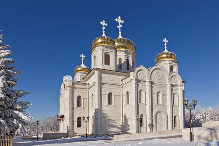 Orthodox temple with golden domes of white stone and covered by snow against the blue sky.