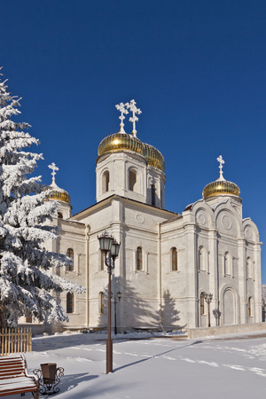 Orthodox temple of white stone dusted with snow against the blue sky. Stock Photo