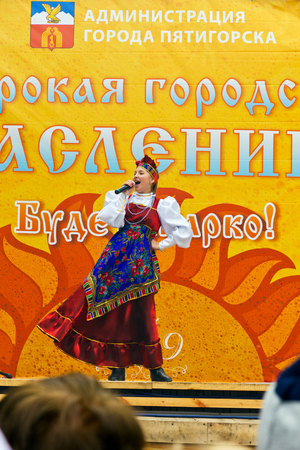 Pyatigorsk, Russia. March 2, 2014: Maslenitsa. See off winter. Girl on price in a bright dress sings on a city holiday.