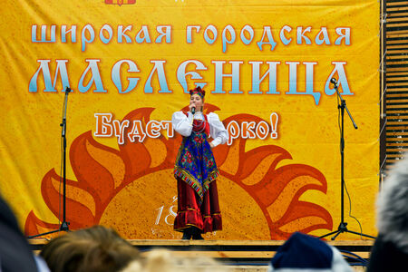 Pyatigorsk, Russia. March 2, 2014: Maslenitsa. See off winter. Girl in a bright dress sings on a city holiday. Editorial